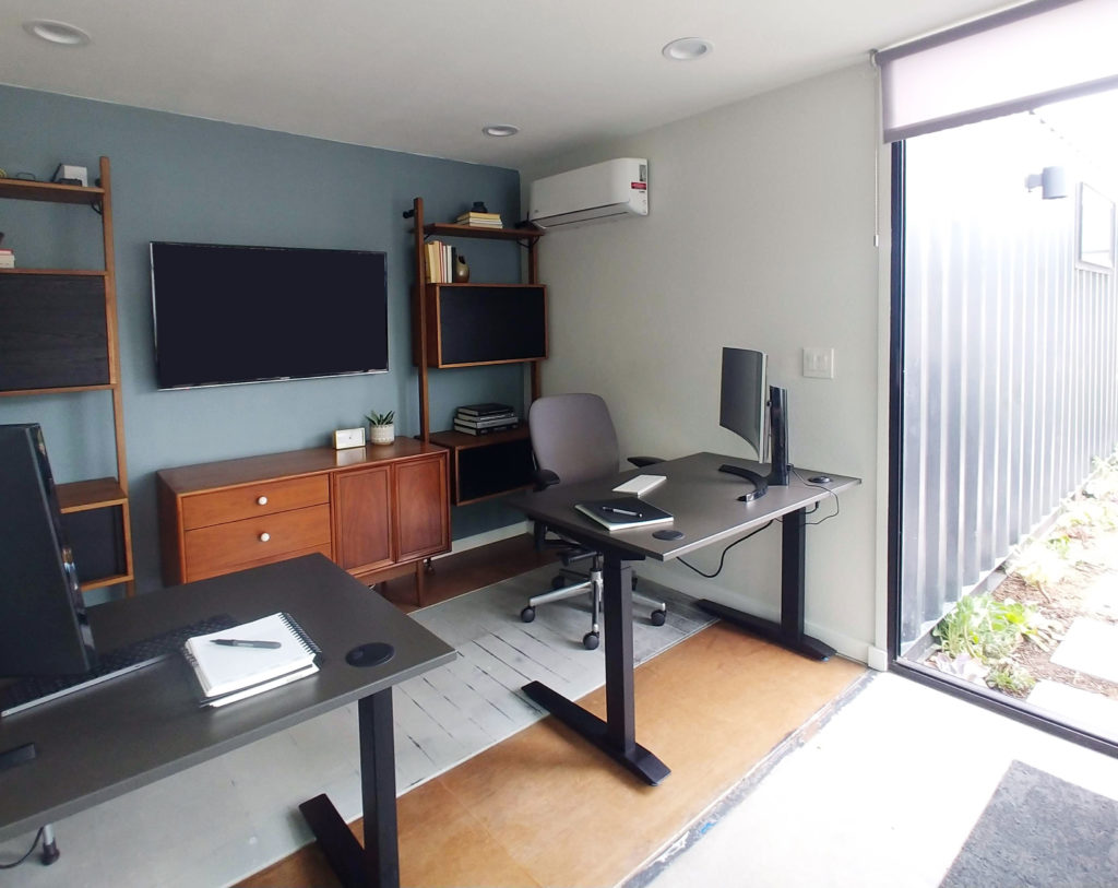 A photo of two black jarvis desks with notebooks, nice office chairs, filing cabinets and an extra screen—all of the work from home essentials