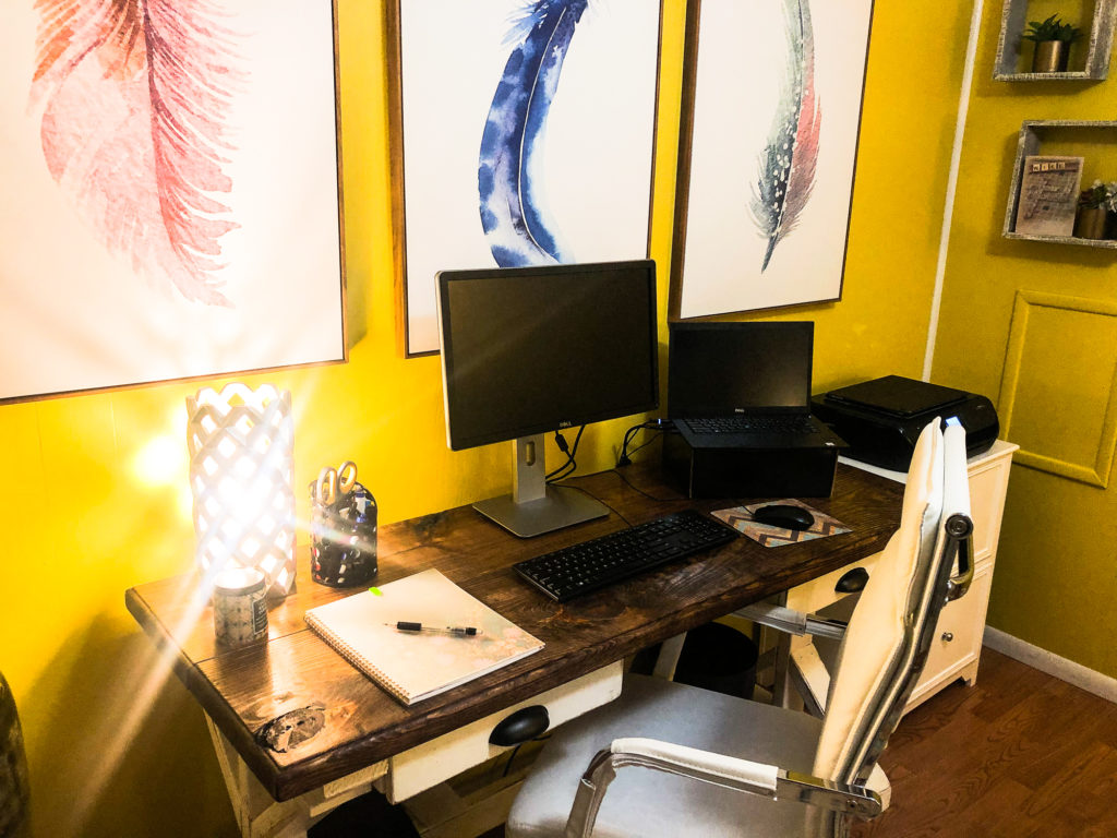 A desk with a notepad a monitor and a laptop in a home office with yellow walls, and three large photos of pink and blue feathers behind the monitors