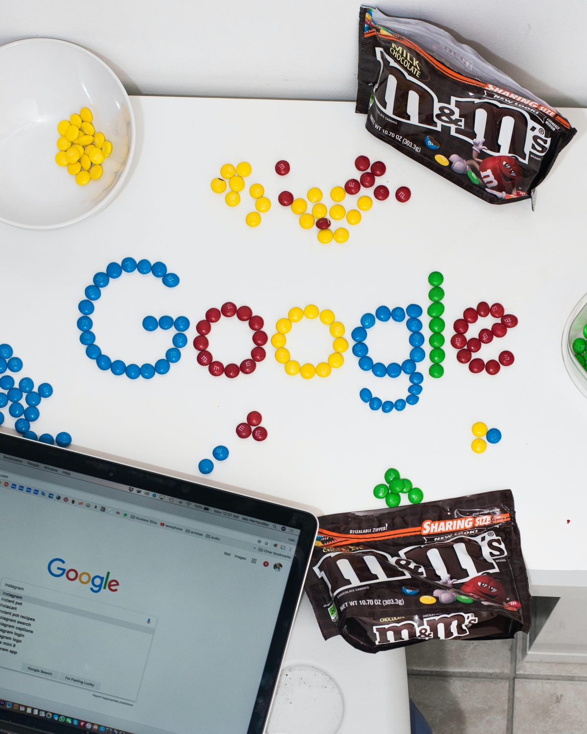 "The word ""Google"" being spelled out on a white desk with mm's. In the shot are two open bags of mm's and a laptop open with google on the screen."